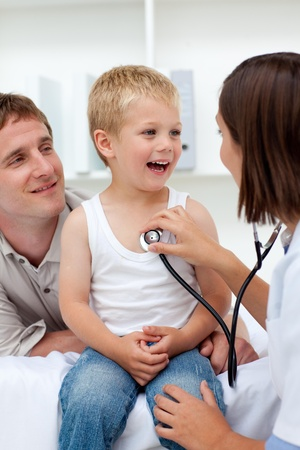 Female doctor examining a boy with his father in tow