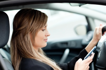 Beautiful businesswoman sending a text while driving