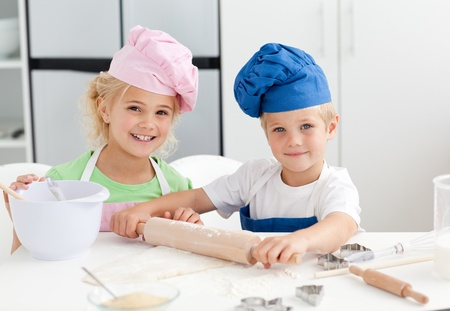Happy brother and sister preparing a dough standing in the kitchen