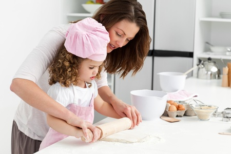 Photo for Mother and daughter using a rolling pin together - Royalty Free Image