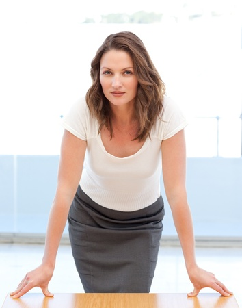 Confident businesswoman posing leaning on a table