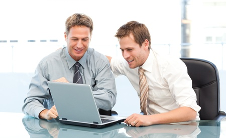Two happy businessmen working together on a laptop sitting at a table