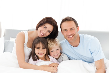 Foto de Portrait of a happy family sitting on the bed  - Imagen libre de derechos