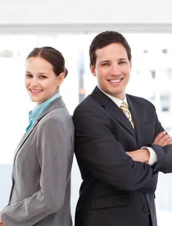 Photo pour Happy businessman and businesswoman posing back to back - image libre de droit