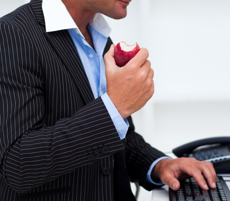 Close-up of a businessman eating a fruit