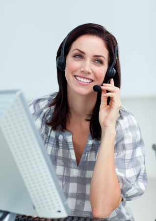 Radiant businesswoman with headset on working at a computer