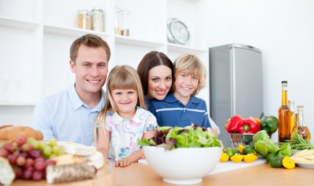 Photo pour Smiling parents and their children preparing dinner together - image libre de droit