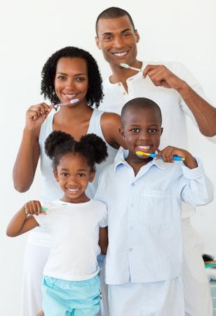 Photo pour Smiling family brushing their teeth - image libre de droit