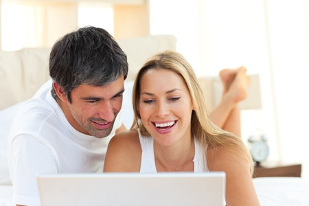 Close-up of lovers using a laptop lying on bed