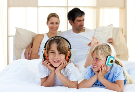 Brother and sister listening music with headphones