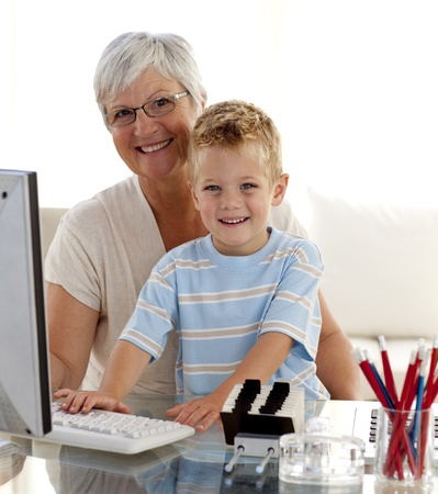 Happy grandson using a computer with his grandmother