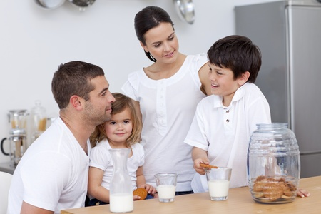 Parents and children eating biscuits and drinking milk