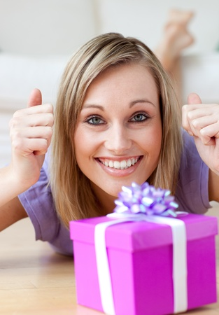 Excited woman looking at a gift lying on the floor