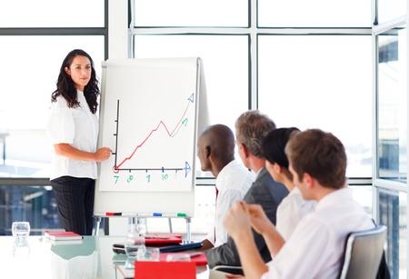 Foto de Businessswoman reporting to sales figures in a meeting - Imagen libre de derechos
