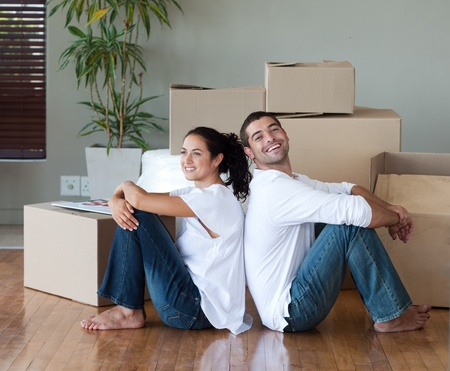 Bright couple with unpacking boxes moving to a new house