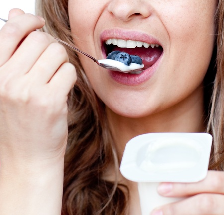 Beautiful woman eating a yoghurt