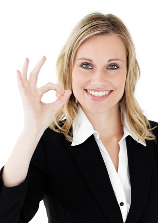 Confident youngl businesswoman showing OK sign against a white background