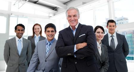 Foto de Senior manager with folded arms accompanied by his team - Imagen libre de derechos