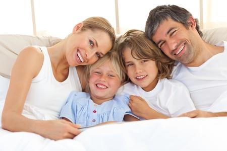 Foto de Happy family reading a book on bed - Imagen libre de derechos