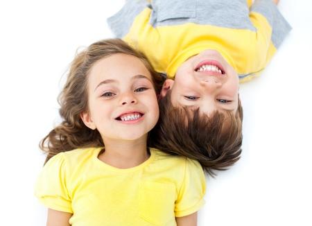 Smiling siblings lying on the floor