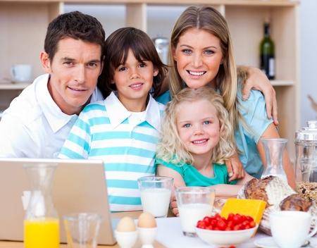 Joyful family using laptop during the breakfast