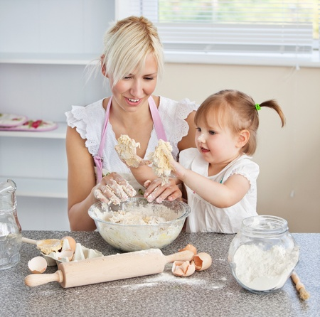 Simper woman baking cookies with her daughter