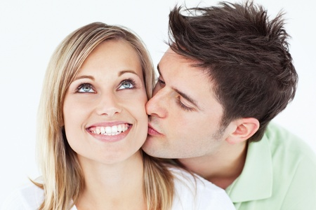 Careful man kissing his smiling girlfriend against a white background