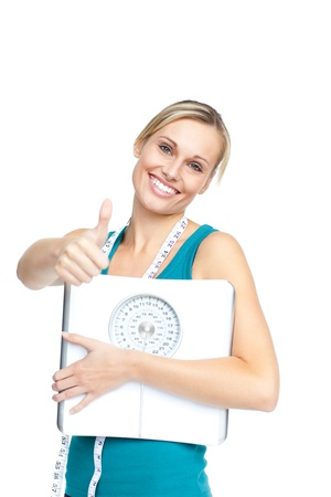 Attractive young woman holding a weight scale looking at the camera