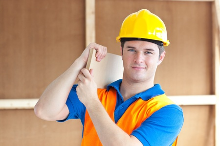 Confident young male worker with a yellow helmet carrying a wooden board