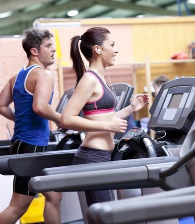 Foto de Healthy couple running on a treadmill in a sport centre - Imagen libre de derechos
