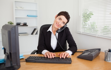 Photo pour Professional secretary answering the phone in her office - image libre de droit