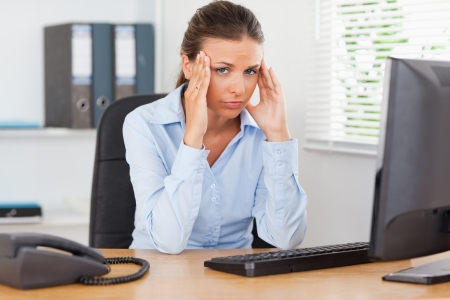 A stressed businesswoman is sitting at workplace in an office while looking into the camera