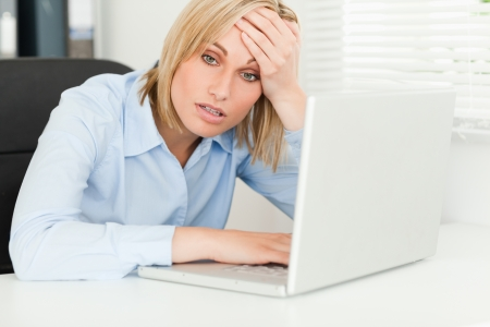 Blonde business woman touching her forehead in disbelieve in her office
