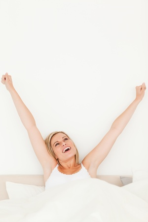 Portrait of a young woman stretching her arms in her bedroom