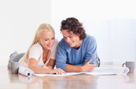 Smiling couple getting ready to move in a new house while lying on the floor