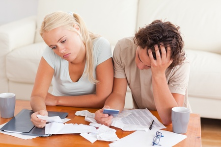Unhappy couple listing expenses in the living room