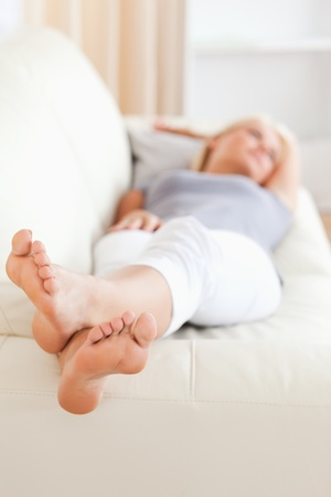 Woman lying on a sofa with the camera focus on her feet