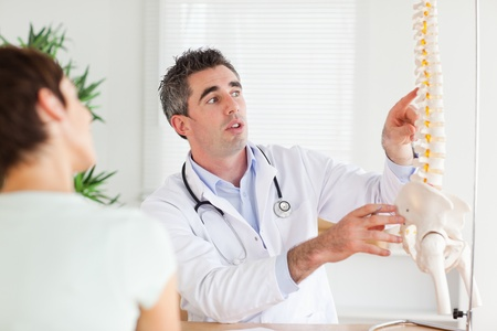 Doctor showing a woman a part of a spine in a room