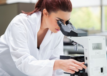 Young scientist looking into a microscope in a laboratory