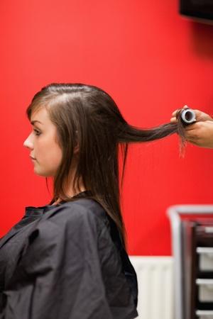 Photo pour Portrait of hands rolling hair with a curler - image libre de droit