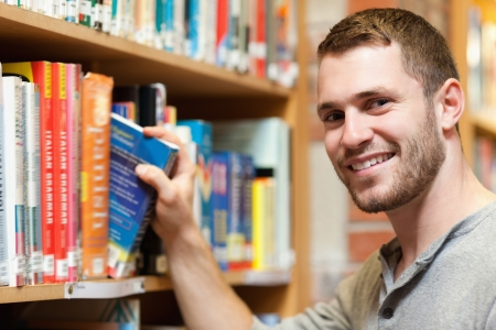 Smiling male student picking a book in a library