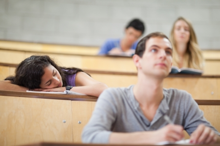 Students listening a lecturer while their classmate is sleeping in an amphitheater