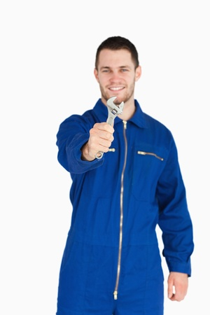 Wrench shown by smiling young mechanic in boiler suit against a white background