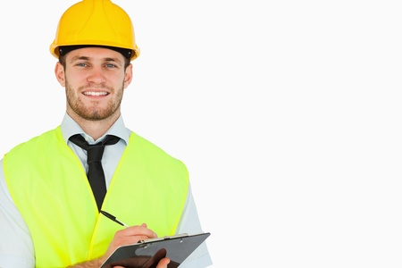 Smiling young lead worker with clipboard against a white background