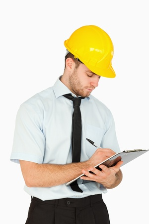 Young lead worker writing on his clipboard against a white background