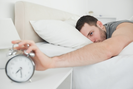 Sleeping attractive man being awakened by an alarm clock in his bedroom