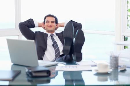 Photo pour Smiling businessman relaxing in his office - image libre de droit