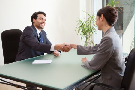 Smiling manager interviewing a good looking applicant in his office