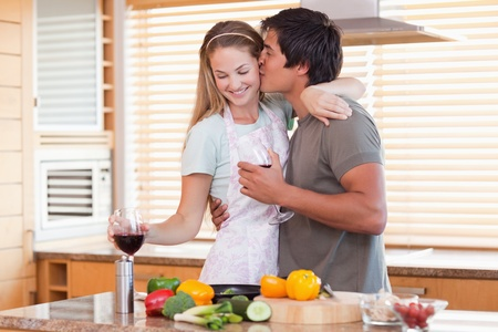 Lovely couple drinking red wine while kissing in their kitchen