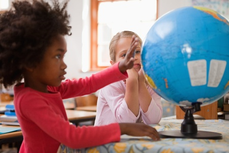 Happy schoolgirls looking at a globe in a classroom